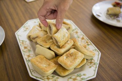 Australian snack, party pies and sausage-rolls on a plate with fingers selecting one.