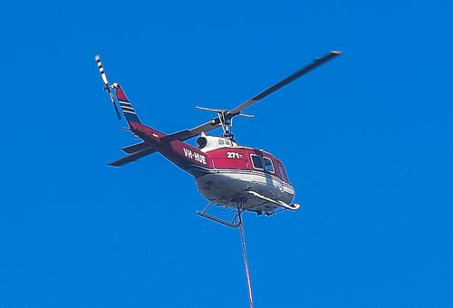 Phil O'Driscoll's UH-1H helicopter waterbombing the Holsworthy blaze on the weekend. (AAP)