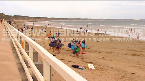 Beach-goers packed up after being warned of the large shark. (9NEWS)