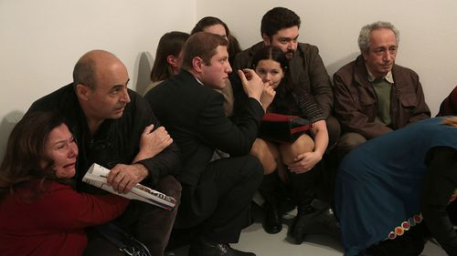 Terrified witnesses huddle in a corner inside the gallery where Andrey Karlov was killed.