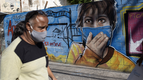A man walks past a mural referencing the COVID-19 pandemic, painted in honour of health workers in Rio de Janeiro, Brazil, Thursday, May 21, 2020. The mural is by graffiti artist Angelo Campos, 39, who has lost two relatives to the new coronavirus. (AP Photo/Silvia Izquierdo)