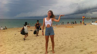 A young woman holds up the storm front as it rolls across Wanda Beach, Cronulla. (Supplied: Hannah Rogers)