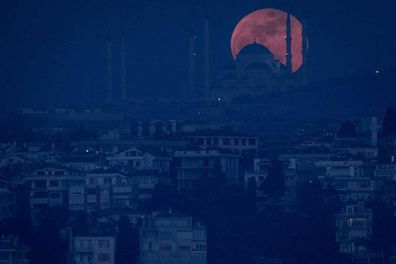 A Super Blue Blood Moon rises behind the Camlica Mosque on January 31, 2018 in Istanbul, Turkey.