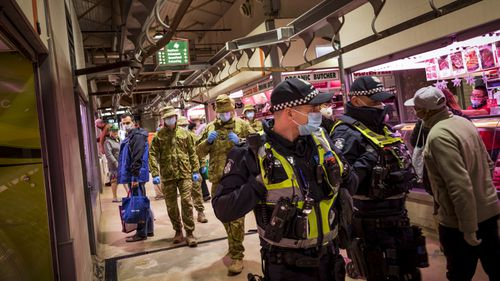 Members of Victoria Police aided by ADF soldiers patrol the Queen Victoria Market in Melbourne