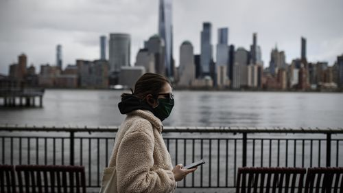 In this April 10, 2020 file photo a woman wearing a face mask sure to CVID-19 concerns walks along the Jersey City waterfront with the New York City skyline in the background.