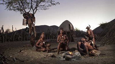 """Evening fire with the Himba: """"This image was taken at dusk in  Otjimaza village, just outside Epupa, Namibia. The days are hot and dusk allows the women to rest and tend to their children. The women warm themselves around the evenings cooking fire as the coals burn, this waiting period allows their babies a chance to be fed before being put to bed for the evening."""" Ben McRae, 3rd place, Australia National Award, 2015 Sony World Photography Awards."""