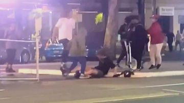 The young teenager sits on the ground as he is attacked by two others, one swinging a metal scooter.