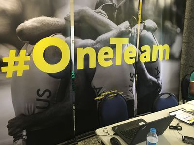The walls of the team's living room are covered in posters with the #OneTeam logo.
