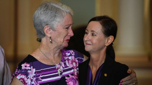 Jo Grant's mother Sandra Kelly (left) embraces Queensland Attorney General Y'vette D'Ath during a press conference at Parliament House. (Image: AAP)