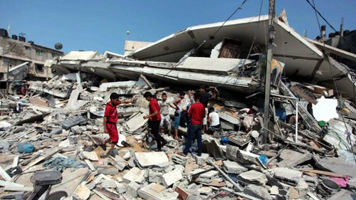 Palestinians inspect rubble in Gaza for anything useful. (Getty)