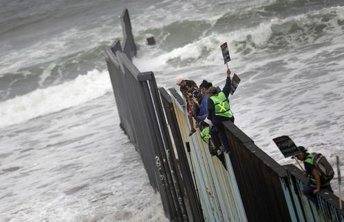 Central American migrants sit on the US-Mexico border wall at its westernmost point, Tijuana, Mexico.