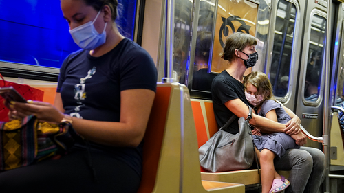FILE - In this Aug. 17, 2020, file photo, a child rests on a subway car while riders wear protective masks due to COVID-19 concerns in New York. (AP Photo/John Minchillo, File)