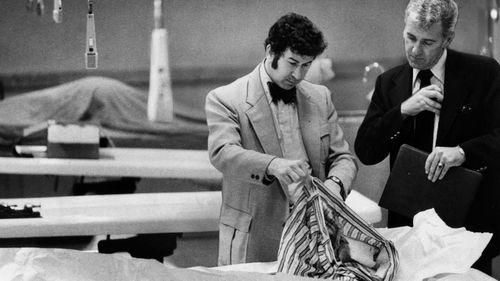 San Francisco homicide inspectors David Toschi, left, and William Armstrong go through a murder victim's clothes