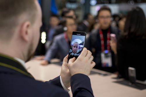 A man clicks his selfie with a smartphone during the Mobile World Congress. (AAP)