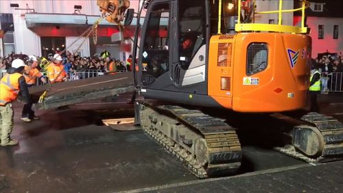 It took about two hours for road workers to carefully dig through bitumen before machinery lifted the lid on Parr's temporary underground home. Picture: 9NEWS