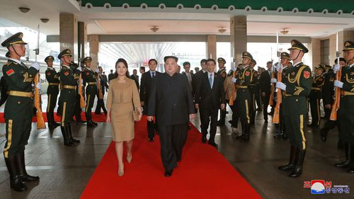 The North Korean leader and his wife get the red carpet treatment in Beijing. Picture: AP