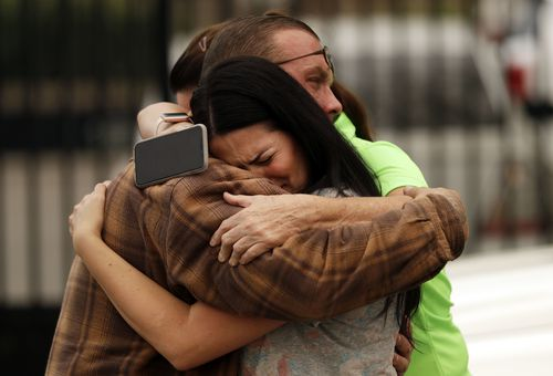 Friends of the Bledsoe family embrace outside of the sheriff's office after hearing news of their deaths. Picture: AAP