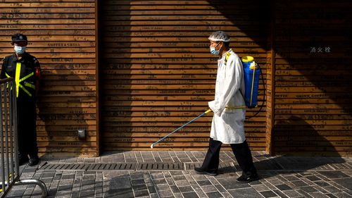 A workers sprays disinfectant to prevent COVID-19 at a shopping area in Beijing.