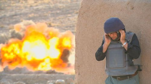 Nine's Mark Burrows reacts to an IED going off in a controlled explosion in Afghanistan.