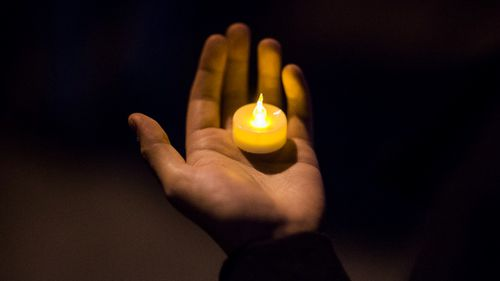 A man holds a candle during an interfaith vigil for peace in response to Manhattan Attack at Foley square. (AAP)