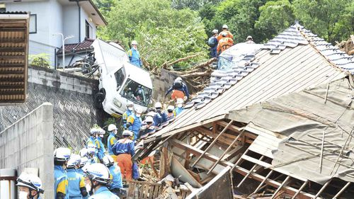 A truck dangles precariously from an incline in Kumano Town, Hiroshima Prefecture. (AAP)