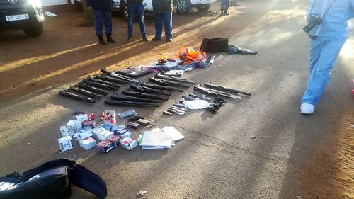 In this photo made available by the South African Police Services (SAPS), confiscated arms and ammunition, lay on the ground at a church in Zuurbekom, near Johannesburg, Saturday, July 11, 2020