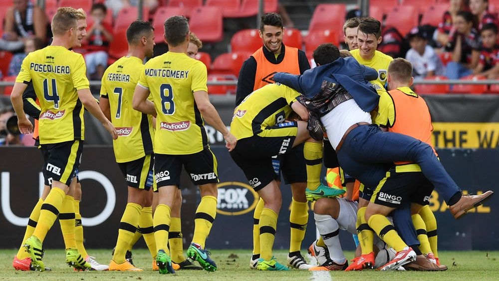 Central Coast Mariners' Roy O'Donovan is mobbed by players and coach Paul Okon after scoring against the Western Sydney Wanderers. (AAP)