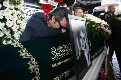 Burcu Gundogar Urfali broke down over top of his wife's coffin at the joint funeral service. (Getty)