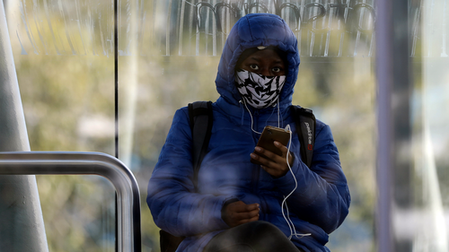A woman wears a face mask at a bus shelter  in the Danoon informal settlement near Cape Town, South Africa, Tuesday, July 14, 2020. (AP Photo/Nardus Engelbrecht)