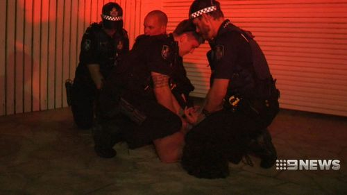 Paramedics work with police to subdue a patient. (9NEWS)