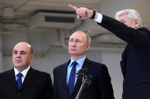 Moscow Mayor Sergei Sobyanin, right, points as he speaks to Russian President Vladimir Putin, center, and Prime Minister Mikhail Mishustin, left, during their visit a call centre of the emergency response centre on control and monitoring of the coronavirus disease.