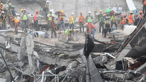 Rescue tream members search for victims in the rubble of a collapsed building. (AAP)