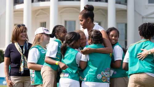 Girl Scouts hugging former US First Lady Michelle Obama during a visit to the White House (Image: AP)