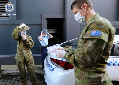 ADF and NSW Police officers put on protective clothing before conducting coronavirus isolation checks.