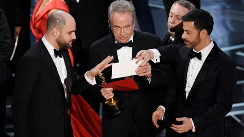 La La Land producer Warren Horowitz (left), presenter Warren Beatty and host Jimmy Kimmel check the envelope. (AAP)