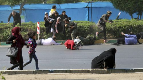 Civilians try to take shelter in a shooting scene, during a military parade marking the 38th anniversary of Iraq's 1980 invasion of Iran, in the southwestern city of Ahvaz, Iran. (AP)