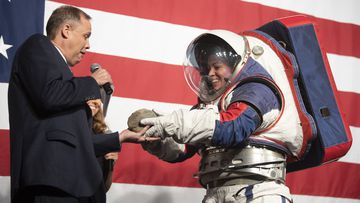 Kristine Dans hands a rock to NASA administrator Jim Bridenstine during a demonstration of the Exploration Extravehicular Mobility Unit (xEMU), one of two NASA spacesuit prototypes for lunar exploration on Tuesday, Oct. 15, 2019, at NASA Headquarters in Washington.