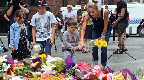 A young family lays flowers in respect at Martin Place. (Getty)