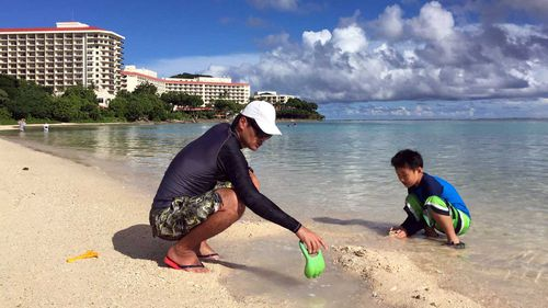 Japanese tourists play on a beach in Guam. (AAP)