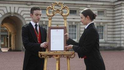 Footmen Stephen Kelly and Sarah Thompson bring out the easel in the forecourt of Buckingham Palace in London to formally announce the birth of a baby boy to the Duke and Duchess of Sussex.