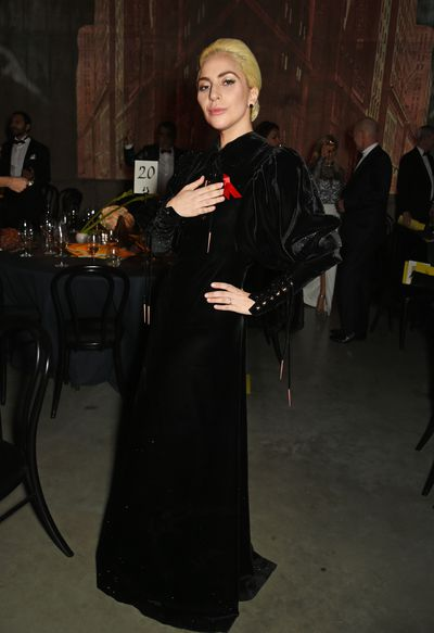 After the Victoria's Secret show Lady Gaga performed in London wearing a gothic black velvet gown accesorised with a red ribbon to raise awareness for AIDS and HIV.