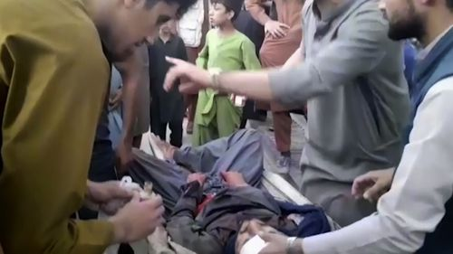 In this frame grab from video, people attend to a wounded man near the site of a deadly explosion outside the airport in Kabul, Afghanistan.