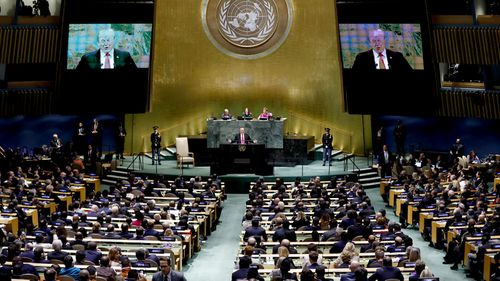 A wide shot shows the room at the General Assembly of the United Nations during President Donald Trump's address.