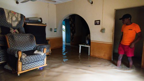 A Nigerian man removes water from his house after heavy rains caused flood in Lagos, Nigeria on June 18, 2020.