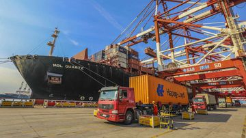 A truck transports a container to be shipped abroad on a quay at the Port of Qingdao. (AAP)
