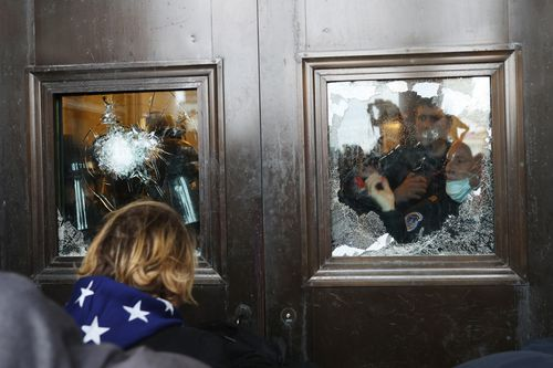 A Capitol police officer looks out of a broken window as protesters gather on the US Capitol Building