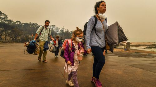 A child in a face mask clutches her mum's hand as they evacuate Mallacoota.