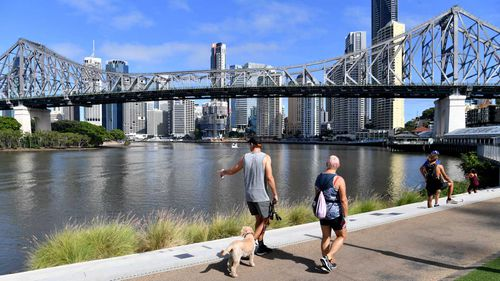 People are seen exercising along side the Brisbane River in Brisbane.