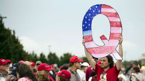 A protesters holds a Q sign waits in line with others to enter a campaign rally with President Donald Trump in August 2014.