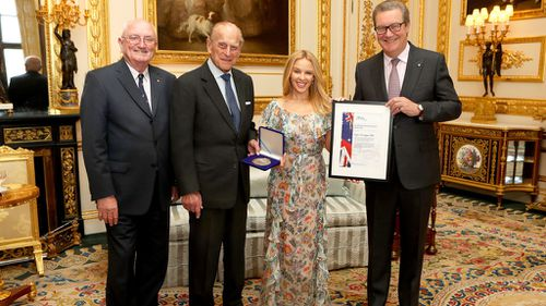 The Duke of Edinburgh presents Kylie Minogue with the Britain-Australia Society Award for 2016, with Britain-Australia Society chairman Peter Benson and Australian High Commissioner to the the UK Alexander Downer. (AAP)